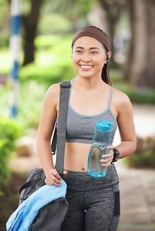 Happy sportswoman with bottle in park