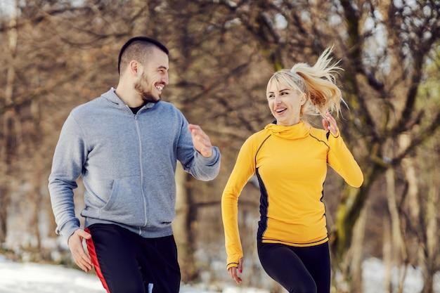 雪の降る冬の日に自然の中で一緒に走っている幸せなスポーティなカップル。関係、冬のフィットネス、健康的な生活