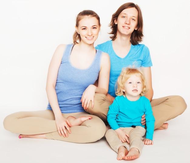Счастливая спортивная семья - мать, отец и маленький сын, позирующие на белом пространстве