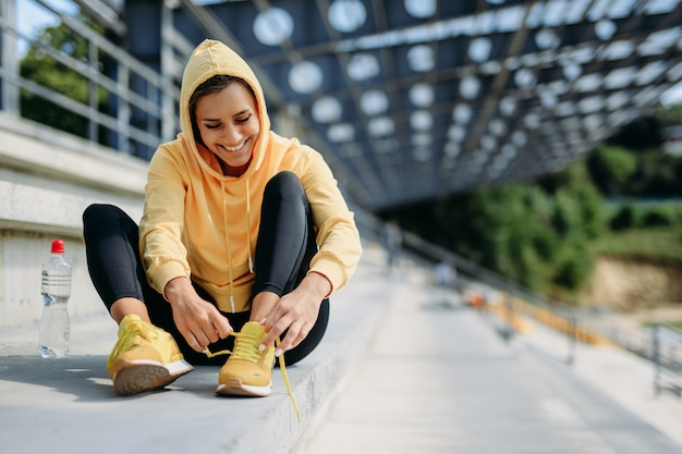 Happy sporty female in yellow hoodie and black leggings sitting on stairs and tying laces on sneakers.