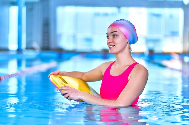 Happy sporty healthy woman in swimming hat and swimsuit learns to swim in sports pool