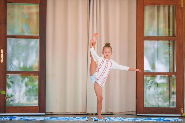 Счастливый спортивный ребенок медитирует на террасе