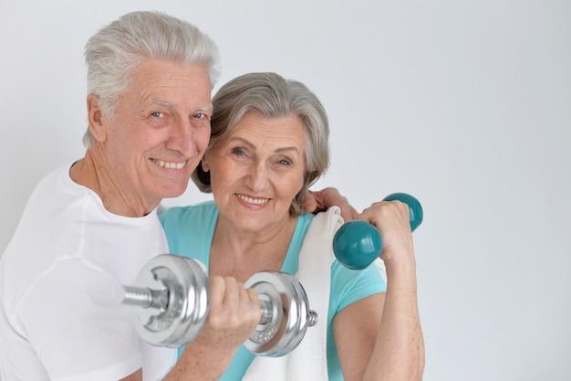 아령으로 운동하는 행복한 스포티 수석 커플