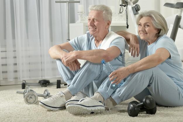 Счастливая спортивная старшая пара отдыхает после тренировки
