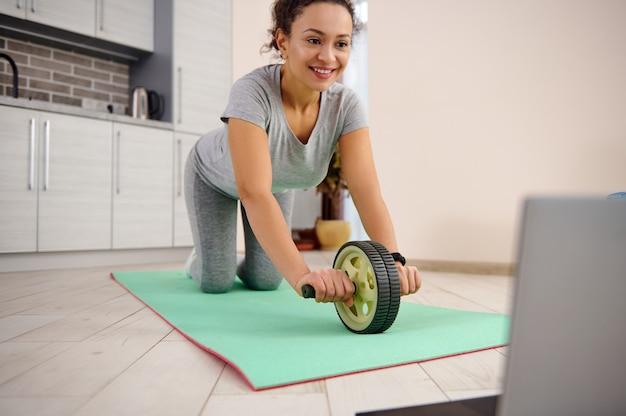 피트 니스 매트에 체조 롤러와 복근 운동을 하 고 행복 한 스포티 한 여자.
