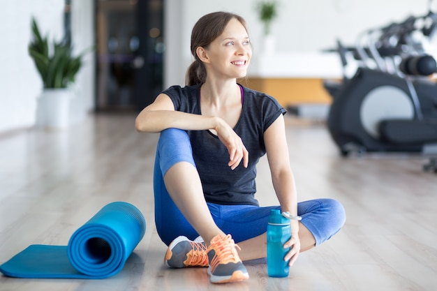 Happy sporty woman on floor with mat and water