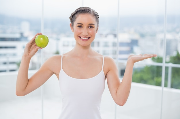 Happy sporty woman holding green apple
