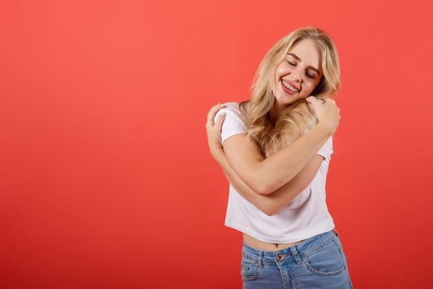 Happy sporty woman is hugging herself