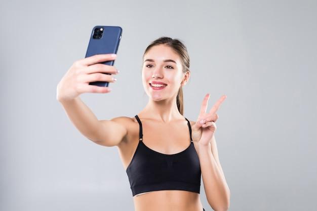 Счастливая sporty женщина делая selfie на изолированном smartphone на белой стене