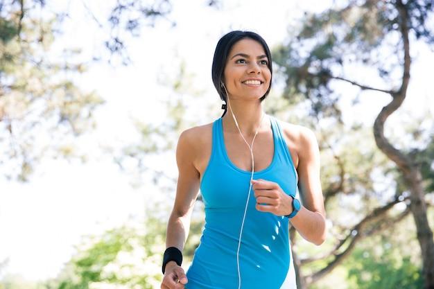 屋外で走っている幸せなスポーティな女性