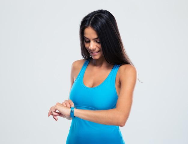 Счастливая спортивная женщина, использующая фитнес-трекер