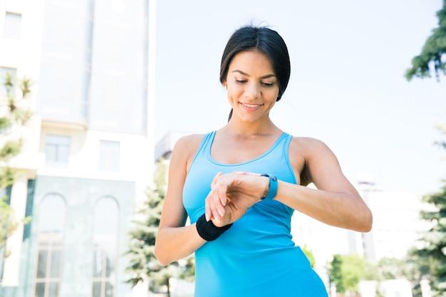 Счастливая спортивная женщина, использующая умные часы