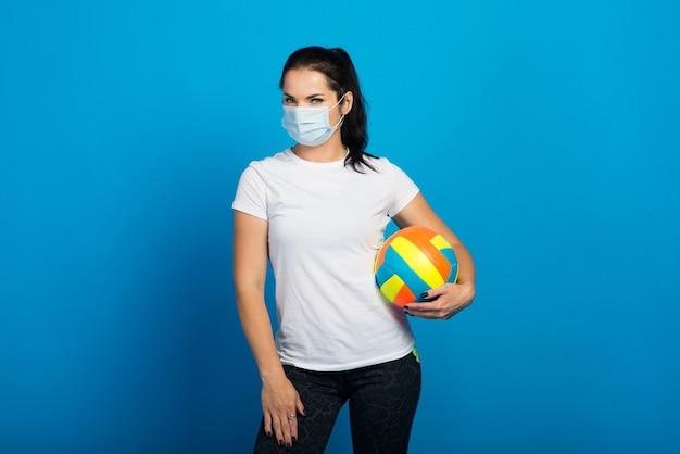 ボールを保持しているコロナウイルスからのフェイスマスクを持つ幸せなスポーティな女性。青で隔離