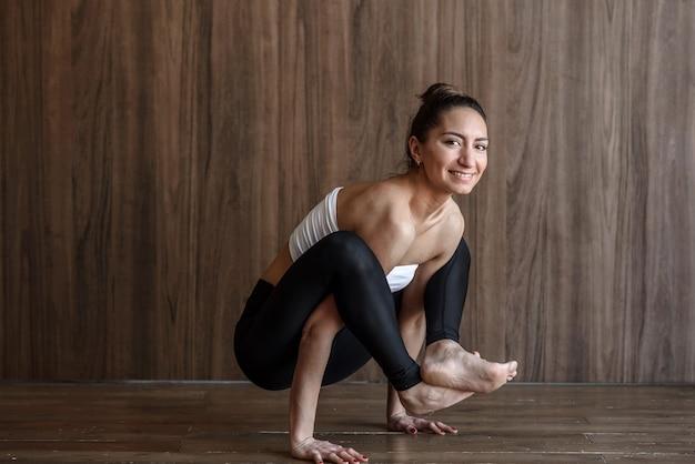 Happy sporty yogi woman practicing yoga in the gym