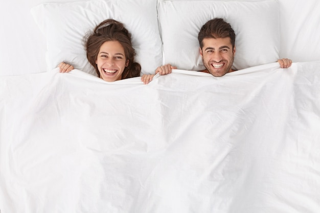 Happy spouses enjoy spending time together, lie under white blanket, have positive expressions and smiles, stay in bed, awake after sleep or nap early in morning feel renewed after deep healthy night,