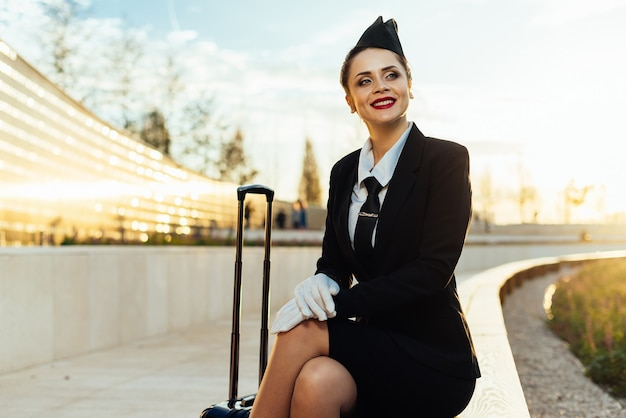 Happy stewardess girl in uniform sits in park, looks up to the sky and thinks about flights