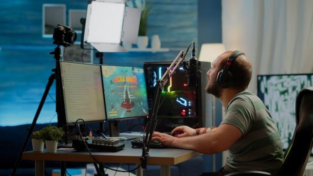 ゲームのホームスタジオでプロのマイクで話しているスペースシューターオンライン競争に勝つ幸せなストリーマー男。トーナメント中にストリーミングチャットを開いてオンラインビデオゲームをプレイするゲーマー