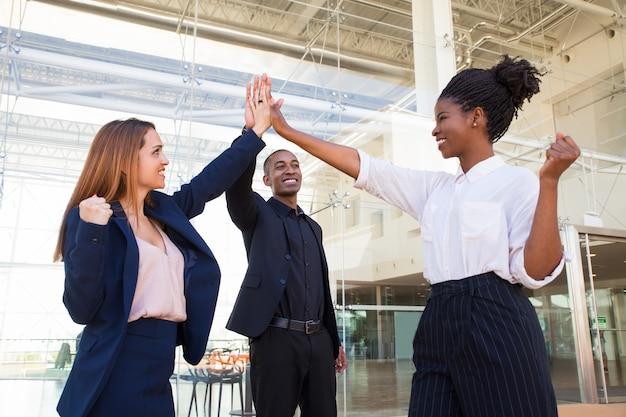 Счастливая сильная бизнес-команда делает высокие пять в офисе