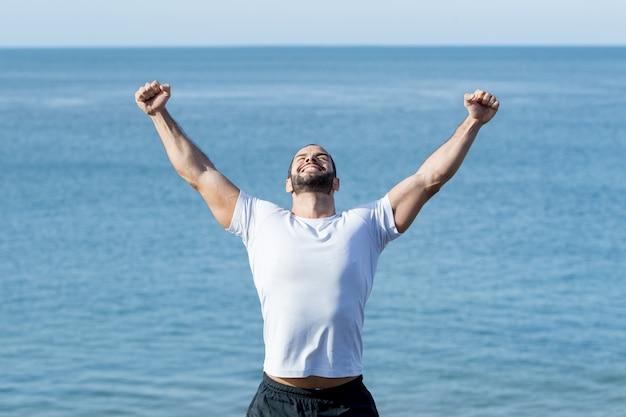 Happy strong man celebrating sport success at sea