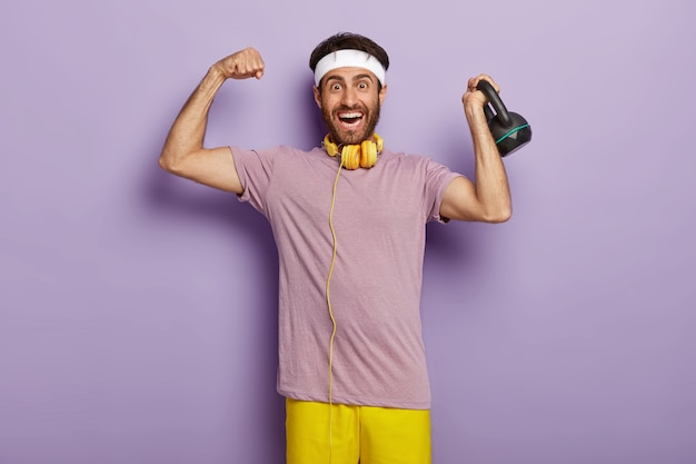Happy strong man lifts weight in sport gym, shows muscles