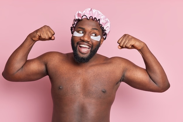 Happy strong smiling man raises arms shows biceps stands naked indoor against pink wall undergoes cosmetic procedures wears moisturising patches under eye water proof bath hat