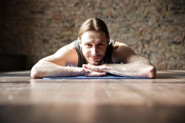 Happy strong sportsman in gym lies on floor
