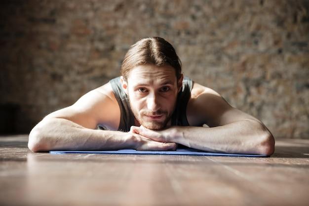 Счастливый сильный спортсмен в тренажерном зале лежит на полу