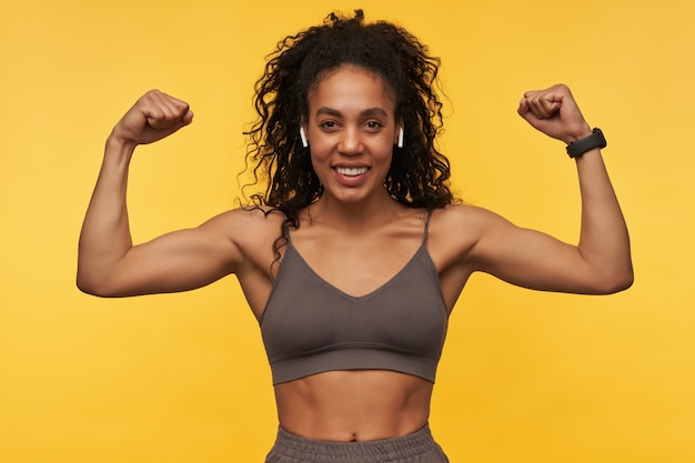 Happy strong young sportswoman with wireless earphones standing and showing biceps muscles isolated over yellow wall
