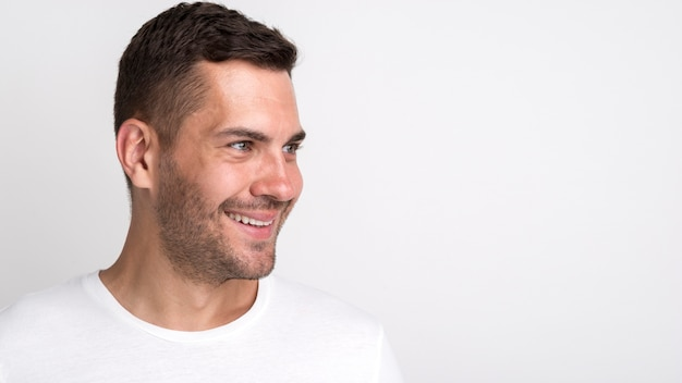 Happy stubble young man looking away standing against white background