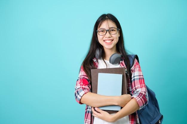 Счастливый студент. веселая азиатская девушка, улыбаясь в камеру, стоя с рюкзаком в студии на синем фоне. снова в школу концепции.