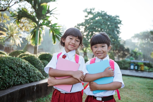 カメラに微笑んで制服を着た幸せな学生の友人