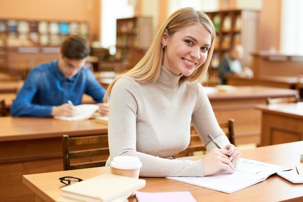 Счастливая девушка студента наслаждаясь временем в библиотеке