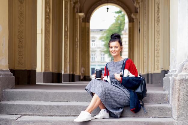 Счастливая девушка студента держит бумажный стаканчик пока сидящ на внешних лестницах.