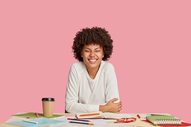 ピンクの壁に対して机でポーズをとって幸せな学生の女の子