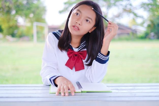 学校の戸外に座っている本を持つ幸せな学生の女の子アジアの女の子