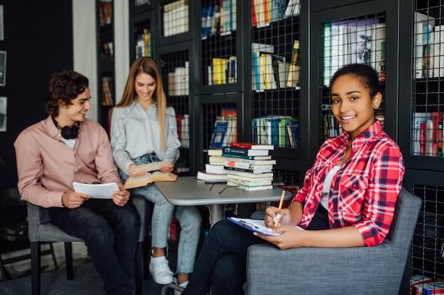Счастливый студент девушка писать в блокнот в библиотеке