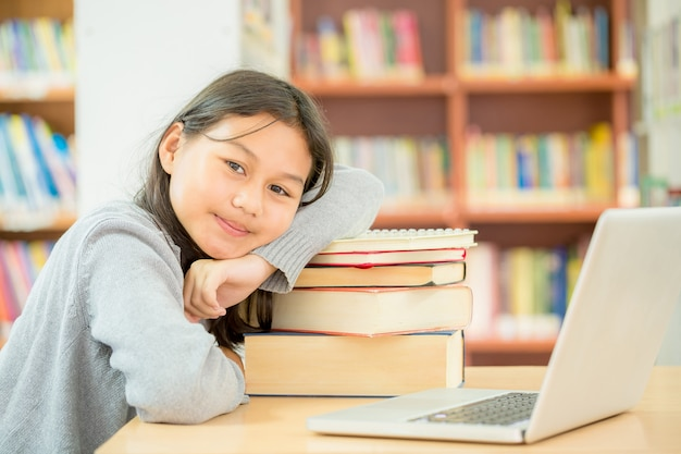 Happy student girl or young girl with book in library.