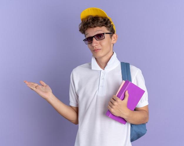 白いポロシャツと黄色の帽子をかぶった幸せな学生の男は、青い背景の上に立っている彼の手の腕を提示してカメラの笑顔を見てノートブックを保持しているバックパックと眼鏡をかけています