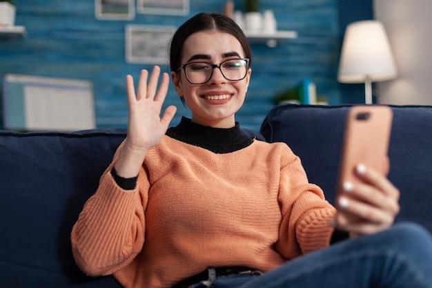 ソーシャルメディアコミュニケーションについて相談している彼女の友人とスマートフォンでオンラインビデオ通話会議をしている幸せな学生。スクリーン電話で見ているリビングルームのソファに横たわっているティーンエイジャー