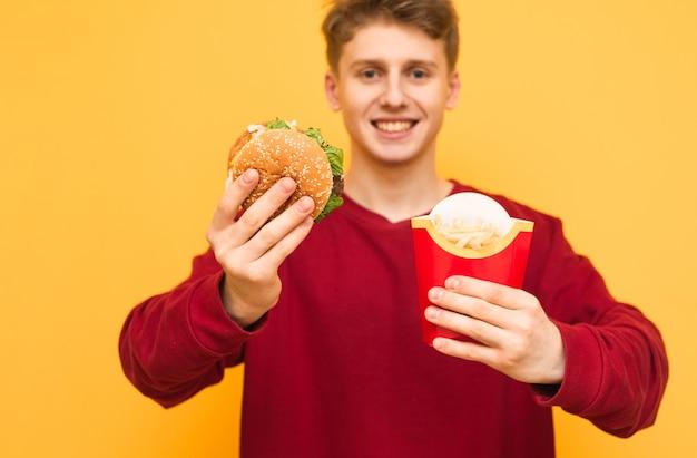 Счастливый студент в повседневной одежде держит в руках гамбургер и картофель фри