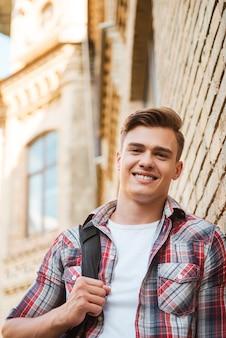 幸せな学生。片方の肩にバックパックを運び、レンガの壁に寄りかかって笑っているハンサムな若い男のローアングルビュー
