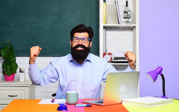 大学生の教室試験で幸せな学生または男性教師のひげを生やした教師が行く