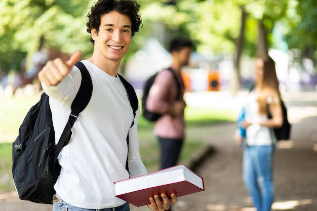 自信を持って笑顔と親指をあきらめて屋外で幸せな学生