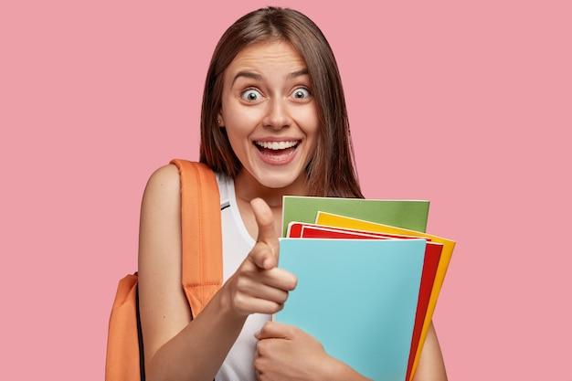 분홍색 벽에 포즈를 취하는 행복 한 학생
