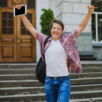 Happy student posing with hands up