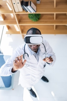 Счастливый студент, тестирующий гаджет виртуальной реальности и стоящий в кабинете