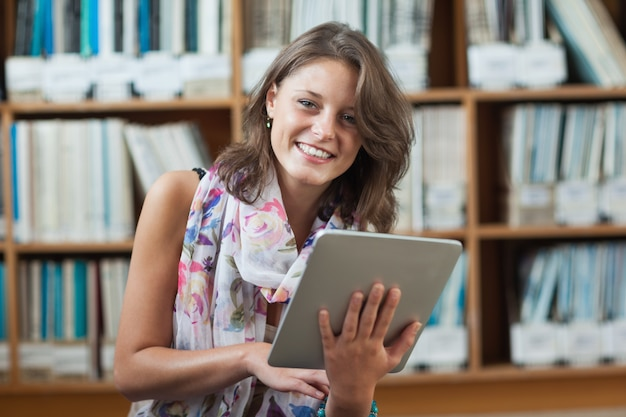 Happy student using tablet pc against bookshelf in library