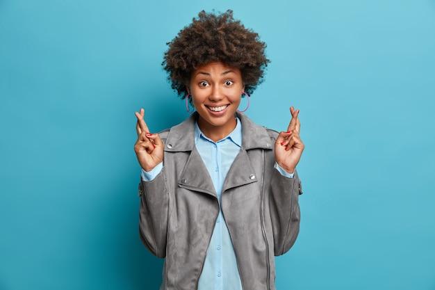 Uno studente felice con l'acconciatura afro spera di superare l'esame con successo, incrocia le dita per avere fortuna, esprime desideri, anticipa risultati positivi, indossa abiti alla moda, posa