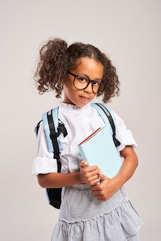 Happy student with backpack holding a book