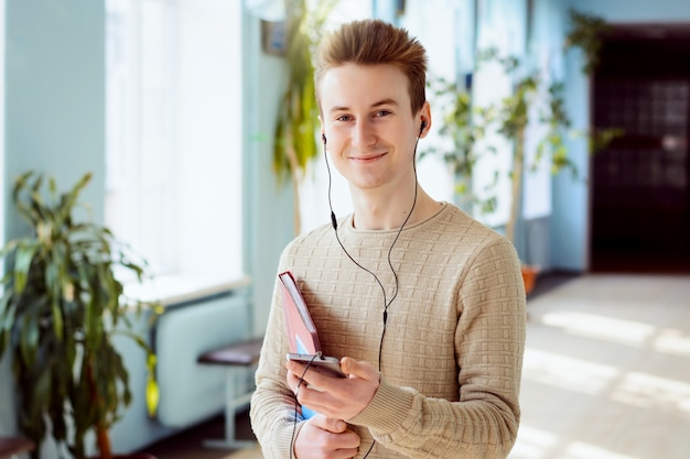 Happy student with mobile phone, earphones in his ears and books in his hands looking to the camera